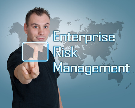 Young man press digital Enterprise Risk Management button on interface in front of him