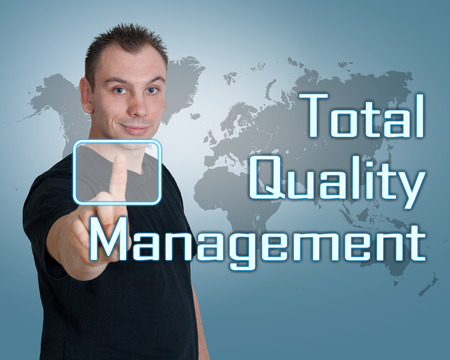 Young man press digital Total Quality Management button on interface in front of him