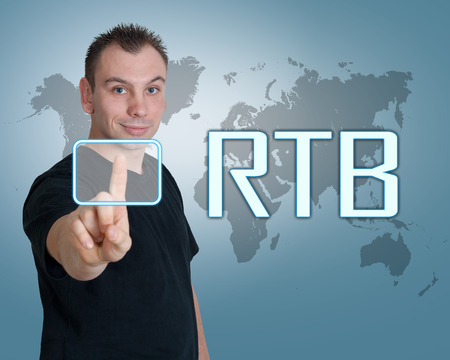 bidding: Young man press digital RTB - Real Time Bidding button on interface in front of him Stock Photo