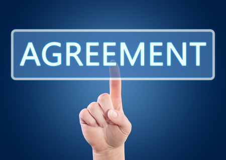 concur: Hand pressing Agreement button on interface with blue background.
