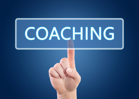 Hand pressing Coaching button on interface with blue background.