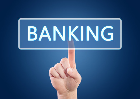 Hand pressing Banking button on interface with blue background. photo