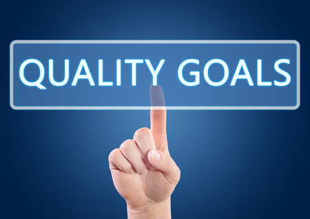 Hand pressing Quality Goals button on interface with blue background. photo