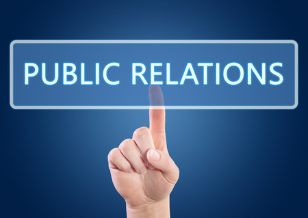 Hand pressing Public Relations button on interface with blue background. photo