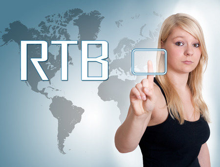 bidding: Young woman press digital RTB - Real Time Bidding button on interface in front of her Stock Photo
