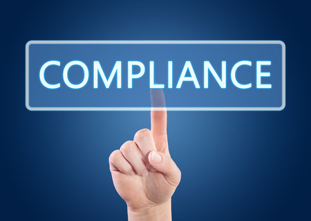 compliant: Hand pressing Compliance button on interface with blue background. Stock Photo