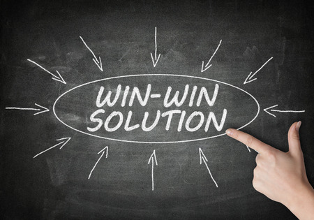 Win-Win Solution process information concept on black chalkboard with a hand pointing on it..