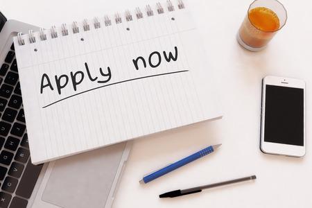 Apply now - handwritten text in a notebook on a desk - 3d render illustration.