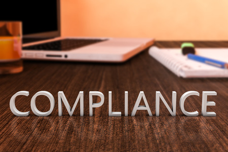 Compliance - letters on wooden desk with laptop computer and a notebook. 3d render illustration. Stock Photo