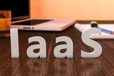IaaS - Infrastructure as a Service - letters on wooden desk with laptop computer and a notebook. 3d render illustration.