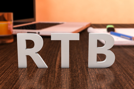 bidding: RTB - Real Time Bidding - letters on wooden desk with laptop computer and a notebook. 3d render illustration.