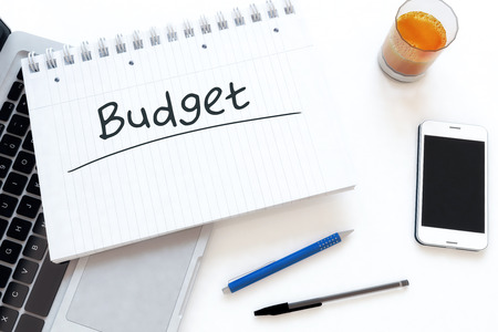 budgets: Budget - handwritten text in a notebook on a desk - 3d render illustration.