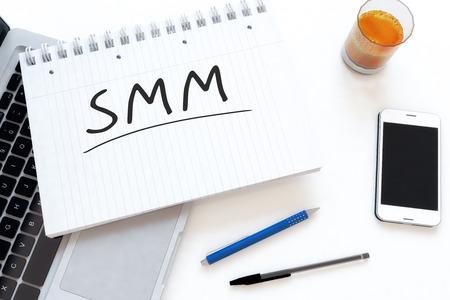 smm: SMM - Social Media Marketing handwritten text in a notebook on a desk - 3d render illustration.
