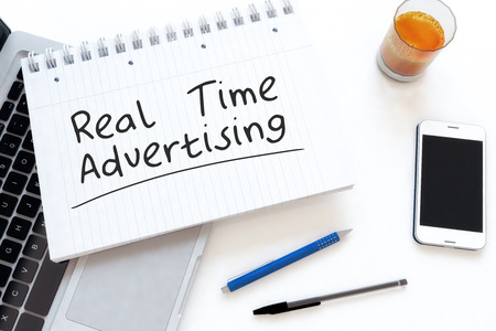 online bidding: Real Time Advertising - handwritten text in a notebook on a desk - 3d render illustration.