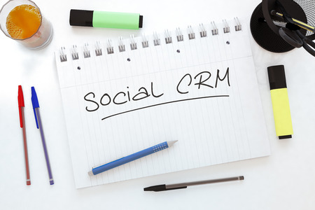 buisnes: Social CRM - handwritten text in a notebook on a desk - 3d render illustration.