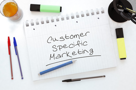 specific: Customer Specific Marketing - handwritten text in a notebook on a desk - 3d render illustration. Stock Photo