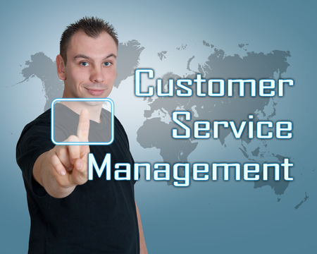 service desk: Young man press digital Customer Service Management button on interface in front of him Stock Photo