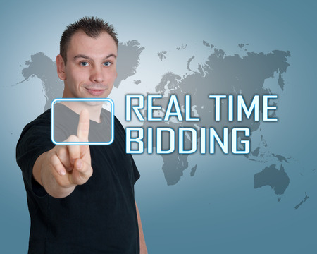 bidding: Young man press digital Real Time Bidding button on interface in front of him Stock Photo