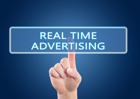 online bidding: Real Time Advertising - hand pressing button on interface with blue background.