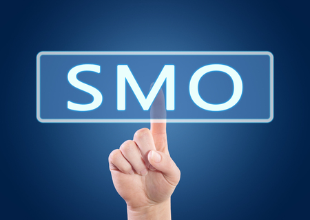 smo: SMO - Social Media Optimization - hand pressing button on interface with blue background.