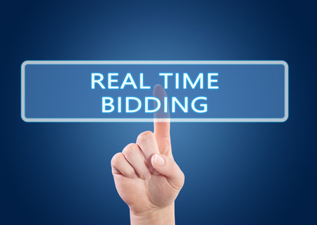 bidding: Real Time Bidding - hand pressing button on interface with blue background.