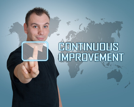 cip: Young man press digital Continuous Improvement button on interface in front of him Stock Photo