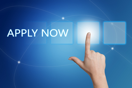 Apply now - hand pressing button on interface with blue background. Stock Photo