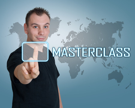 elearn: Young man press digital Masterclass button on interface in front of him Stock Photo