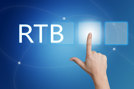 bidding: RTB - Real Time Bidding - hand pressing button on interface with blue background.