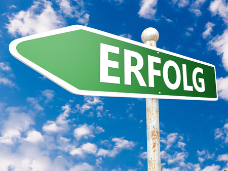 Erfolg - german word for success or achievement - street sign illustration in front of blue sky with clouds. Stock Photo