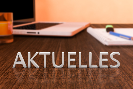 Aktuelles - german word for news, current, topically or updated  - letters on wooden desk with laptop computer and a notebook. 3d render illustration. Stock Photo