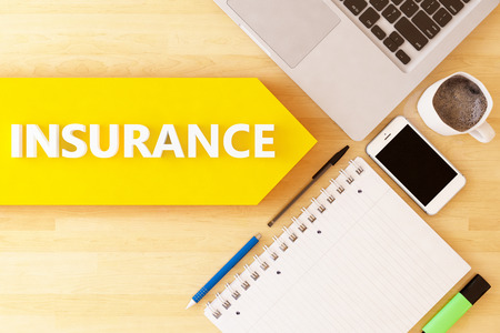 insurer: Insurance - linear text arrow concept with notebook, smartphone, pens and coffee mug on desktop. Stock Photo