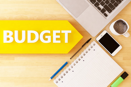 pay cuts: Budget - linear text arrow concept with notebook, smartphone, pens and coffee mug on desktop.