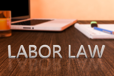 Labor Law - letters on wooden desk with laptop computer and a notebook. 3d render illustration.