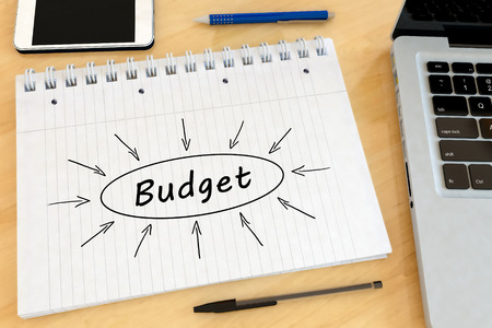 budgets: Budget - handwritten text in a notebook on a desk with laptop and mobilephone- 3d render illustration.