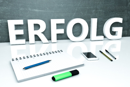 Erfolg - german word for success - text concept with chalkboard, notebook, pens and mobile phone. 3D render illustration. Stock Photo