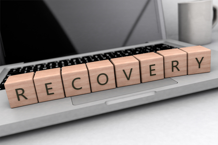 Recovery text concept, lettered wooden cubes on notebook computer- 3D render illustration. Archivio Fotografico
