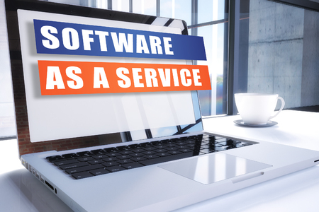 Software as Service text on modern laptop screen in office environment. 3D render illustration business text concept.