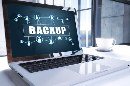 Backup text on modern laptop screen in office environment. 3D render illustration business text concept.
