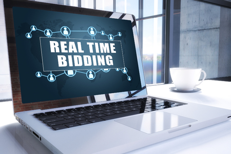 Real Time Bidding text on modern laptop screen in office environment. 3D render illustration business text concept.