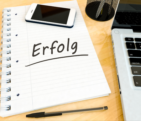 Erfolg - german word for success - handwritten text in a notebook on a desk - 3d render illustration.