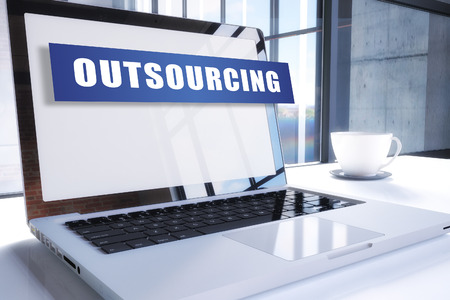 Outsourcing text on modern laptop screen in office environment. 3D render illustration business text concept.