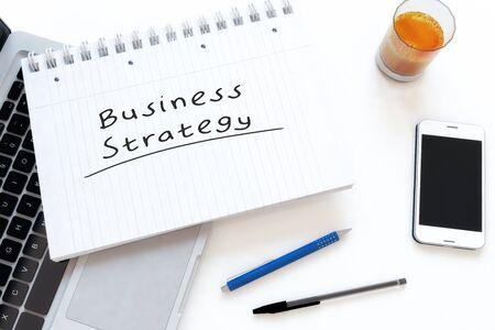 Business Strategy - handwritten text in a notebook on a desk