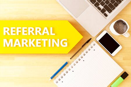Referral Marketing - linear text arrow concept with notebook, smartphone, pens and coffee mug on desktop 写真素材 - 128059672