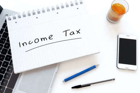 Income Tax - handwritten text in a notebook on a desk - 3d render illustration.