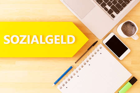 Sozialgeld - german word for social benefits or welfare benefits - linear text arrow concept with notebook, smartphone, pens and coffee mug on desktop - 3D render illustration. Standard-Bild