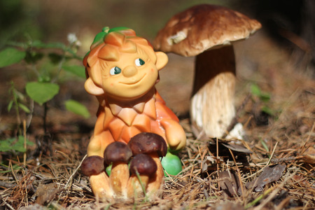 fulvous: Toy Woodsman with brown mushrooms Stock Photo