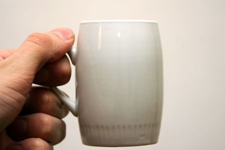 Hand with small coffee cup.