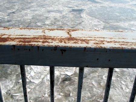 Rusty railing over frozen river.