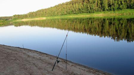 fishingline: Left fishing-rod on a river. Stock Photo